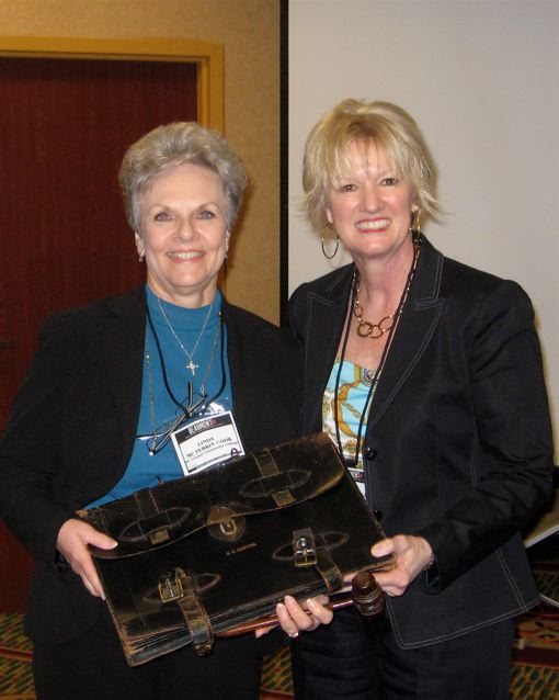 Outgoing CCTE President Peggy Kulesz turns over the briefcase of office to her successor, Linda McFerrin Cook of McClennan Community College